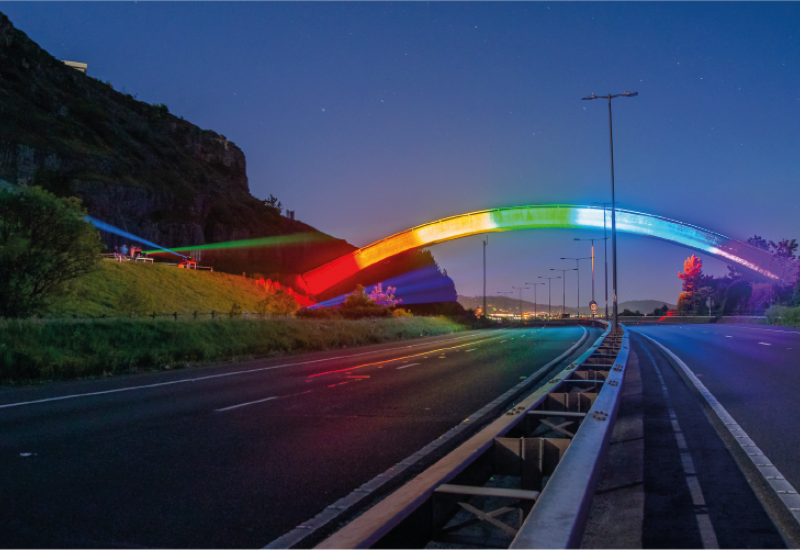 Photograph of a bridge lit up with neon rainbow lights