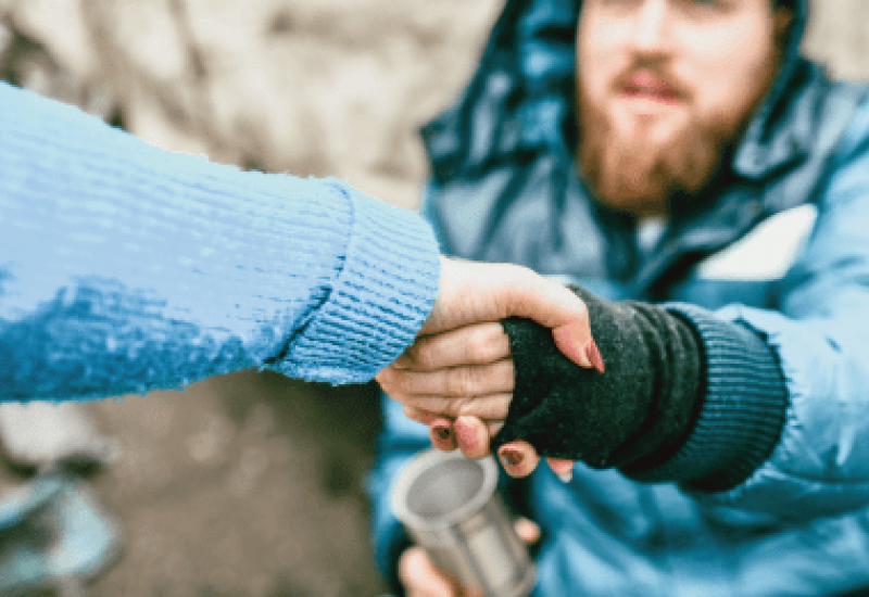Photograph of an outstretched arm grasping the arm of a seated, bearded homeless man
